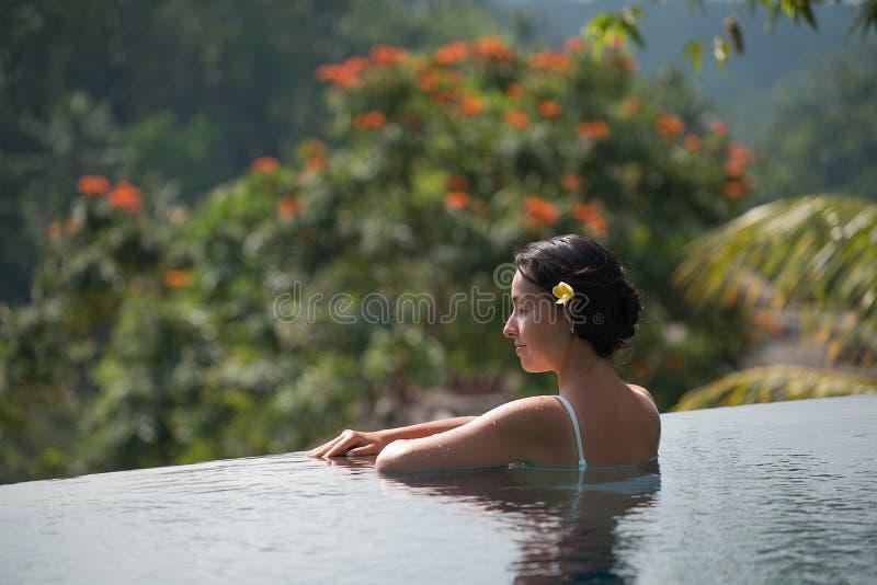 水池的少妇在一栋别墅在Ubud,印度尼西亚村庄  免版税库存照片