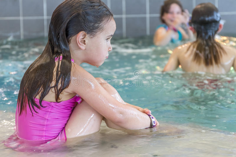 水池的年轻愉快的微笑的女孩 免版税库存照片
