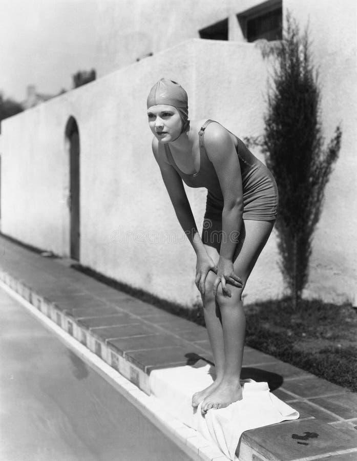 水池边缘的女性游泳者  图库摄影