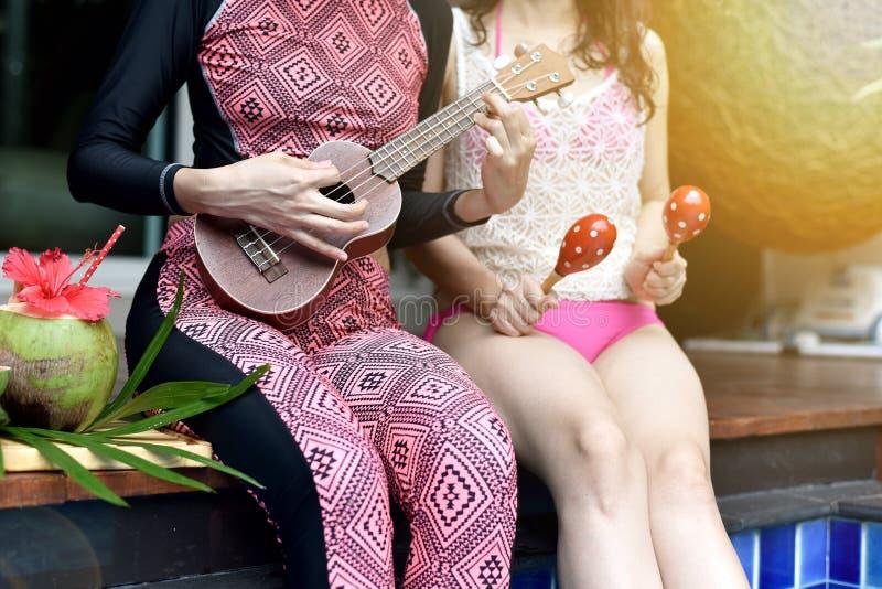 池边聚会,愉快的妇女喜欢演奏比基尼泳装微笑的乐器由游泳池,女朋友和笑 免版税图库摄影