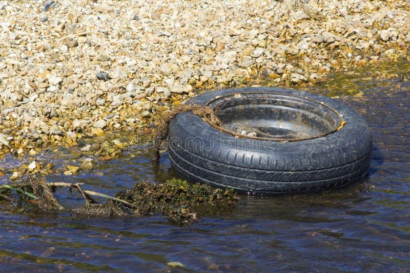 污染在Solent途中的一个废弃的轮胎和外缘一条小小河在南安普敦水靠岸在Titchfield附近在汉普郡 库存照片