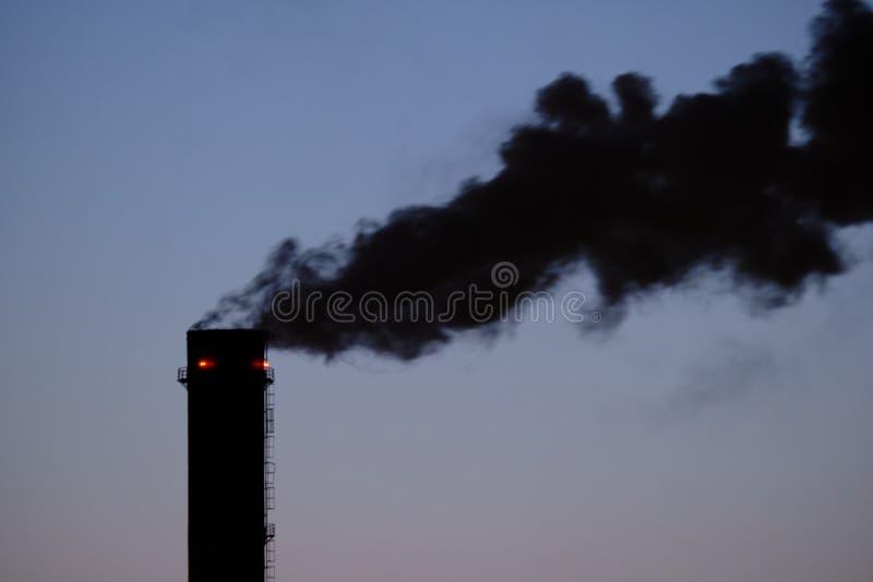 污染大气并且对环境是有害的烟的黑小河从热和能源厂管子出来 免版税库存图片