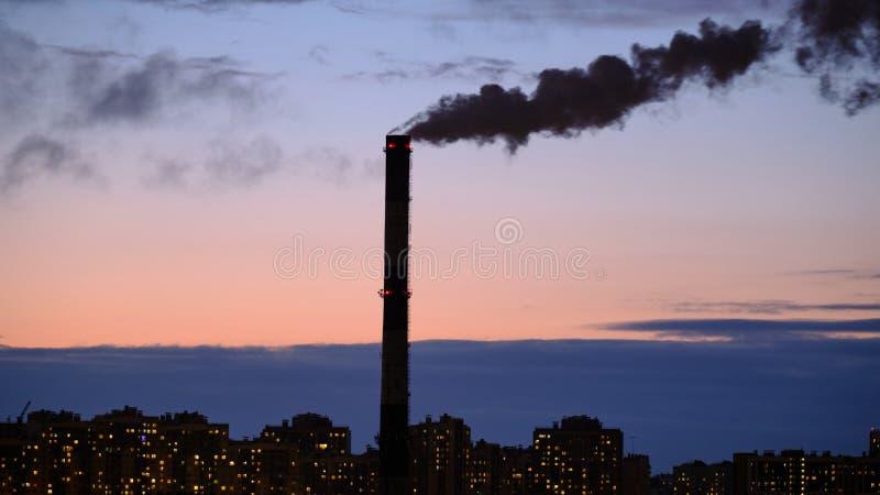 污染大气并且对环境是有害的烟的黑小河从热和能源厂管子出来 免版税图库摄影