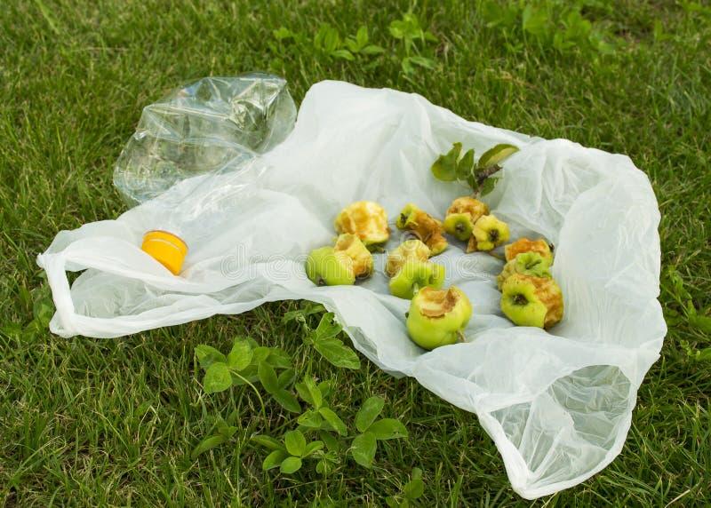 污染的问题 包裹在绿草说谎 在草坪的垃圾 库存图片