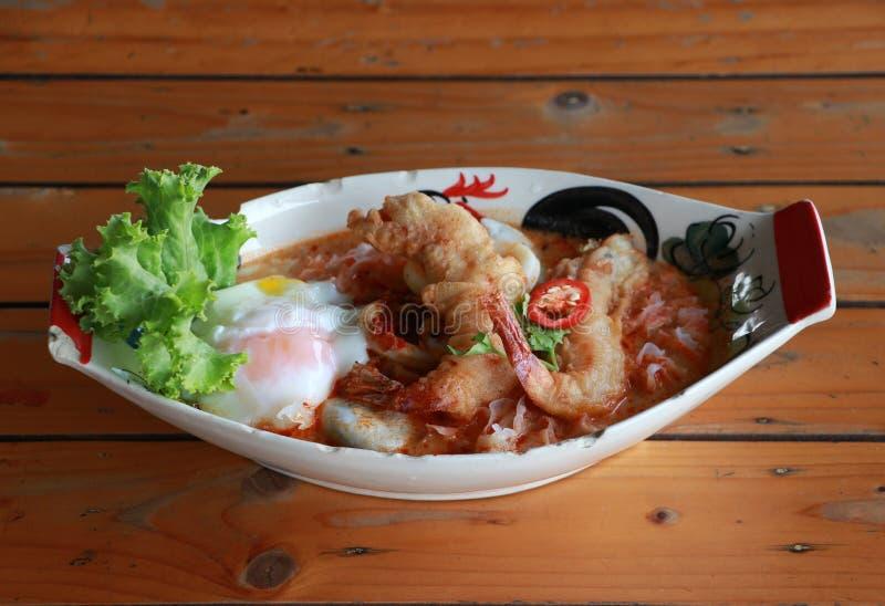 汤姆Goong辣酸汤用在卵形碗的煎酥脆大虾和熔岩鸡蛋 免版税库存图片