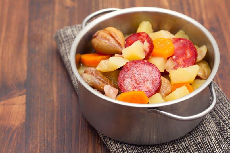 汤栗子用在罐的熏制的香肠在木背景 库存图片