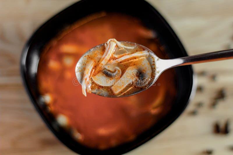 汤用在一个黑碗和金属匙子的蘑菇 免版税库存图片