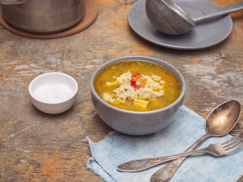 汤用在一块深灰色板材的饺子在一张土气桌上 在背景中是平底深锅用汤,在板材的一个老杓子 免版税库存照片