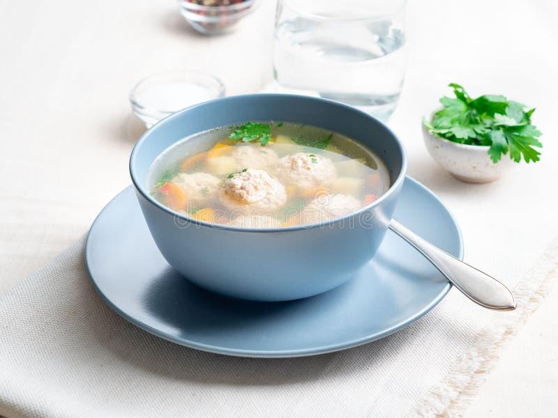 汤用在蓝色板材、白色亚麻制桌布和餐巾,轻的背景,侧视图的丸子 库存照片