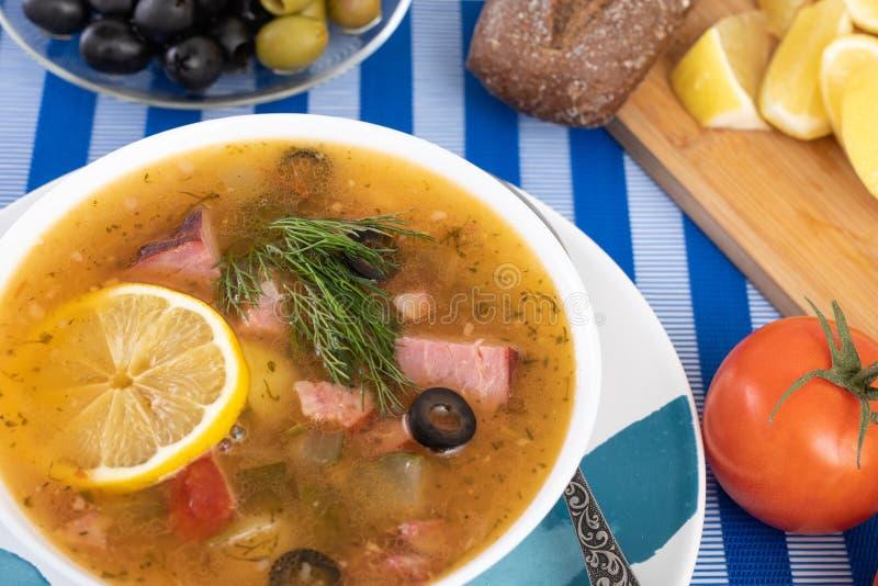 汤用肉,香肠,在wite碗的盐味的黄瓜 黑面包,柠檬,橄榄,在颜色蓝色背景的蕃茄 免版税库存图片