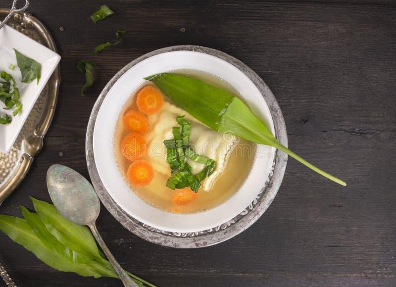 汤用馄饨、红萝卜和ramson在有葡萄酒匙子的银盘生叶 图库摄影