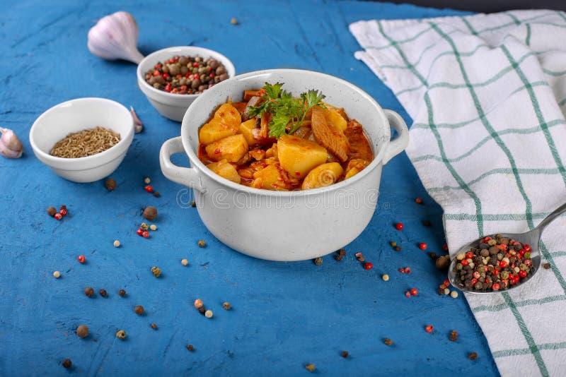 汤藜科冈羊栖菜属植物用肉、土豆、西红柿酱和蘑菇在一个碗在石蓝色背景 免版税库存照片