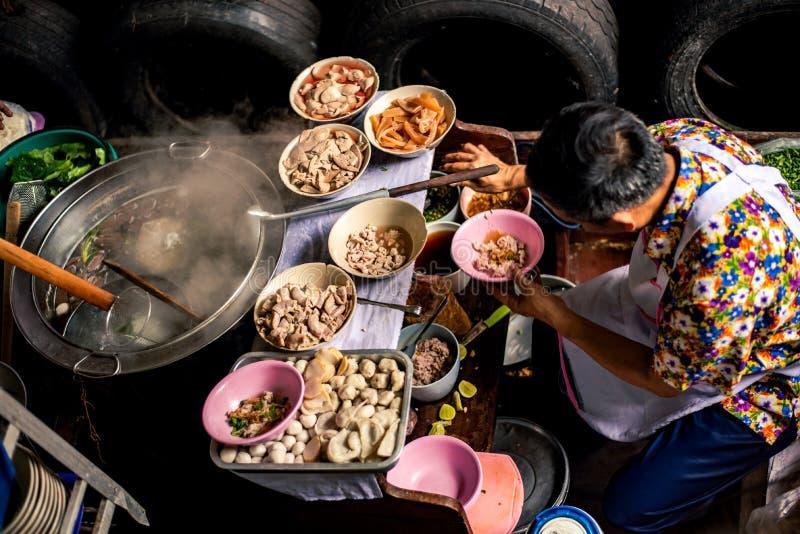 汤面的一个传统供营商在小船的,做汤,在曼谷浮动市场上 免版税图库摄影