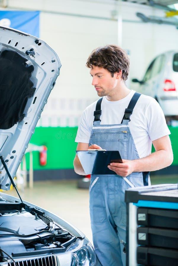 汽车修理师与工具一起使用在服务车间 免版税图库摄影