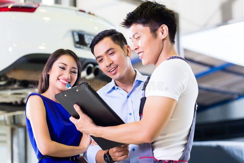 汽车修理师和亚洲顾客夫妇 库存照片