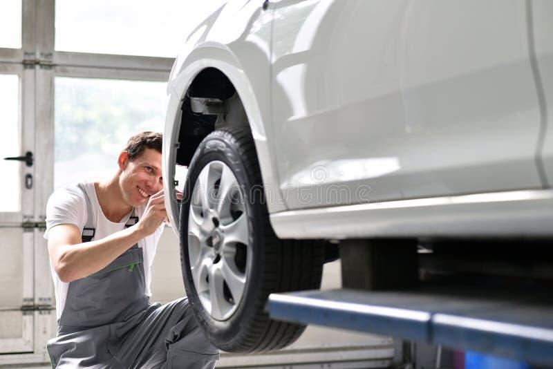 汽车修理师在交通a以后修理车的汽车车体 免版税库存图片