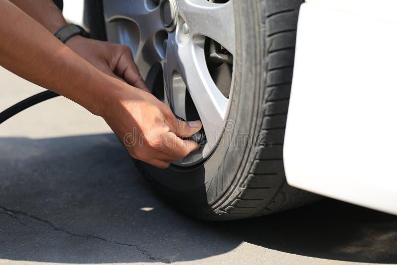 汽车修理师工作和抽空气特写镜头到汽车轮子里在自动修理服务中 库存照片