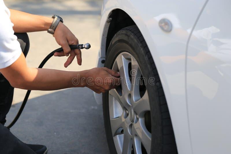 汽车修理师工作和抽空气特写镜头到汽车轮子里在自动修理服务中 免版税库存图片