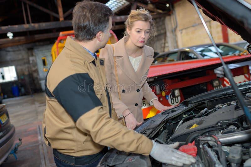 汽车修理师指出往顾客汽车问题 库存图片