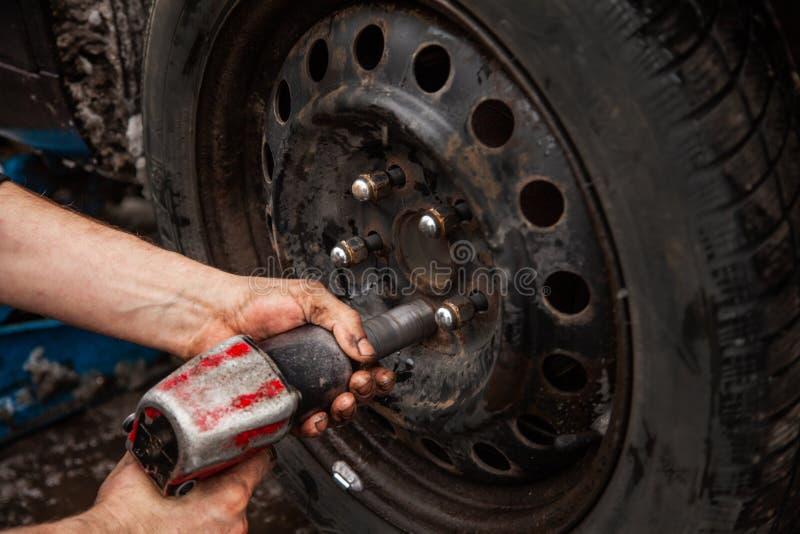 汽车修理师松开车轮,轮子登上 免版税库存图片