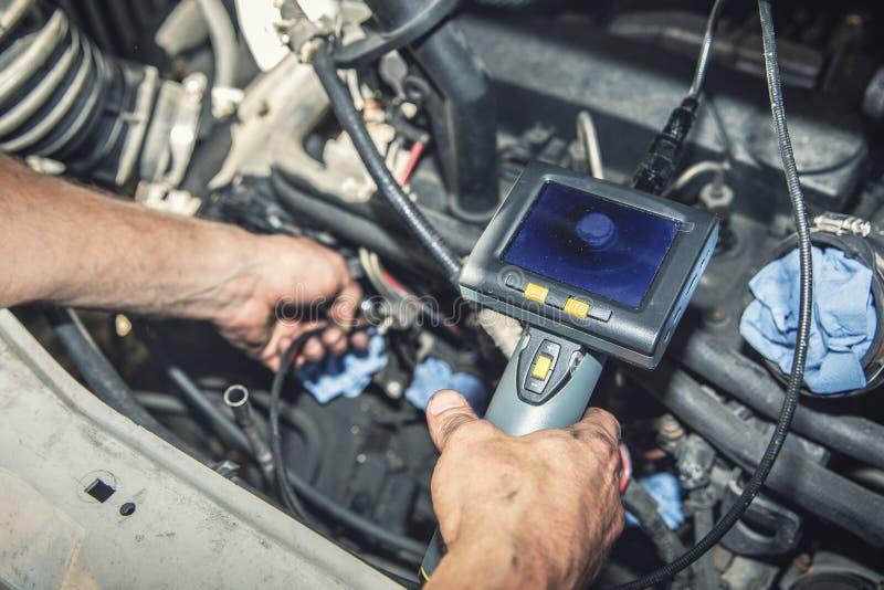 汽车修理师检查有管道探视器的飞行器电动机 库存图片