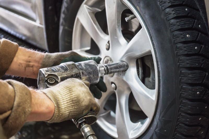 汽车修理师被气动力学的板钳替换被举的汽车车轮在修理公司商店车库驻地 库存照片