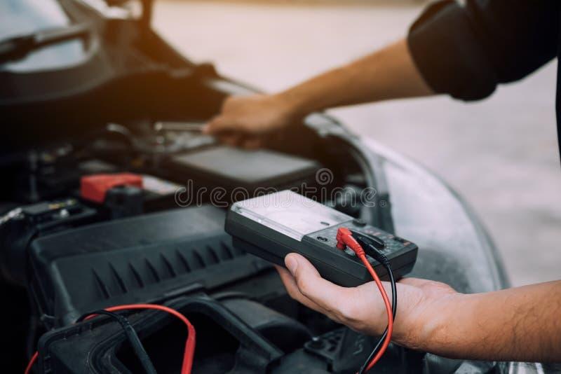 汽车修理师运载一个电池计并且检查引擎的普通保险条款 库存图片