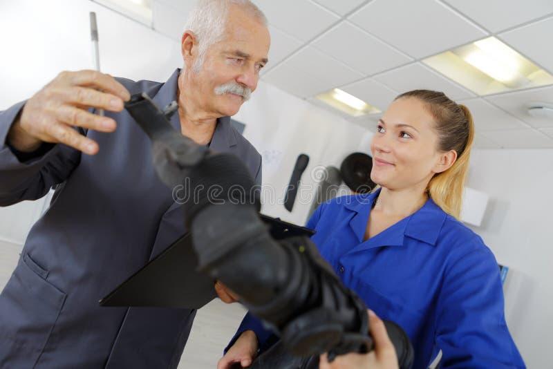 汽车修理店的女性技工与资深工作者 免版税图库摄影