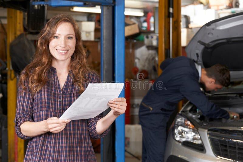 汽车修理店的女性顾客满意对汽车的比尔 免版税图库摄影