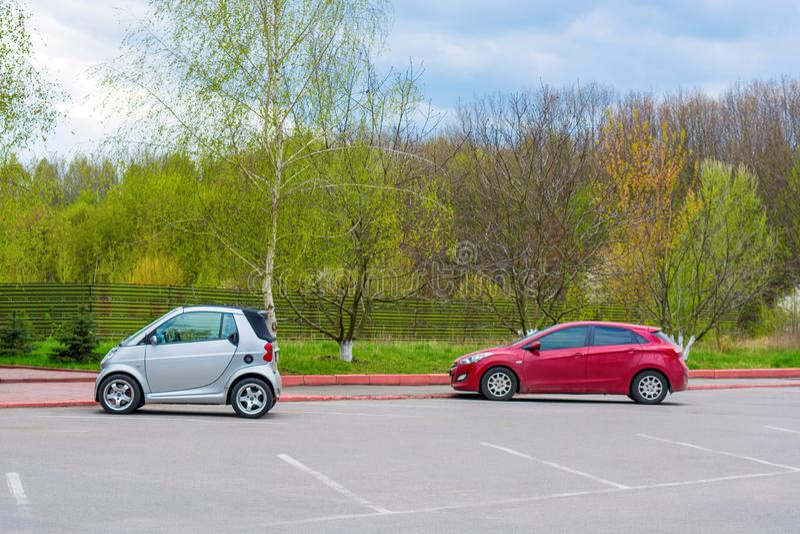 汽车停车处照片与小白色和红色汽车的 库存照片