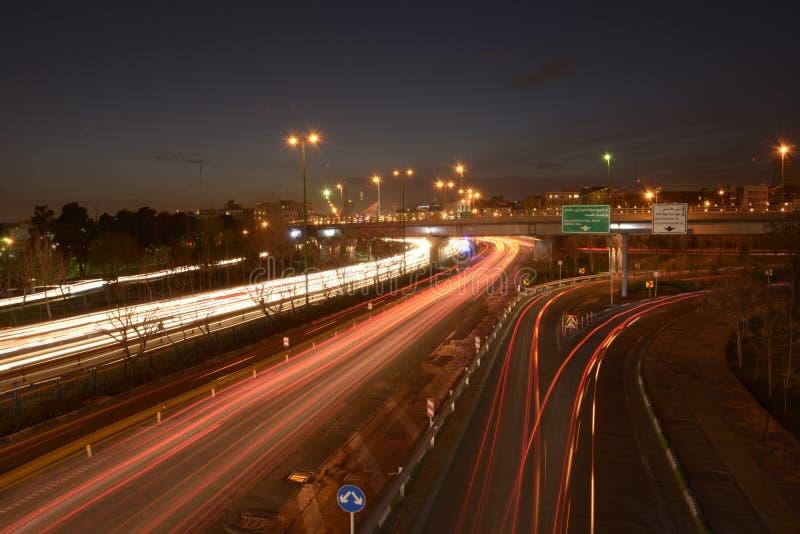 汽车光从移动的车追踪在Resalat高速公路的黄昏 免版税库存照片
