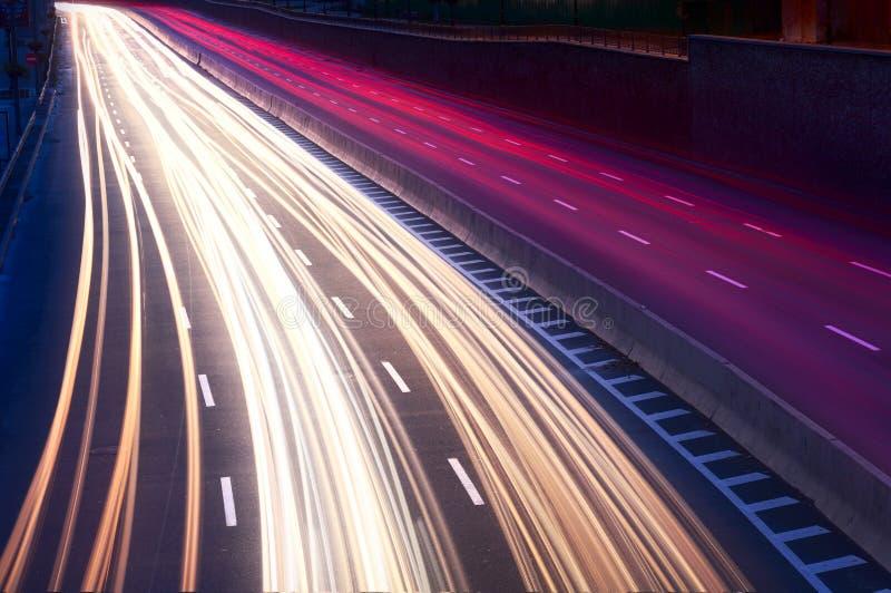 汽车光在城市街道上落后在晚上 库存照片