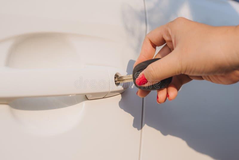 汽车关键妇女 开头车门 妇女的手打开在汽车的一个门 阳光 运输 免版税库存图片