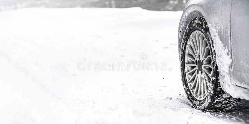 汽车冬天轮胎细节-积雪的路,宽横幅,文本的空的空间离开 在被去除的轮胎的所有商标品牌 库存照片