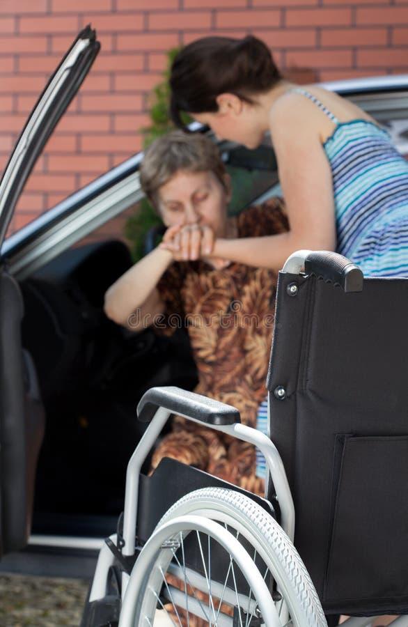 从汽车出来的女孩帮助的残疾妇女 免版税库存照片