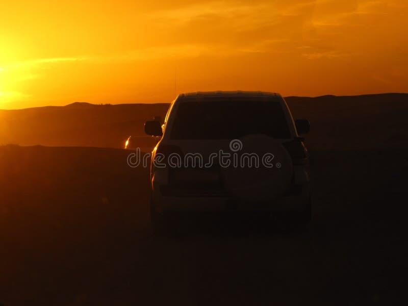 汽车剪影在落日的光芒的沙漠 库存照片