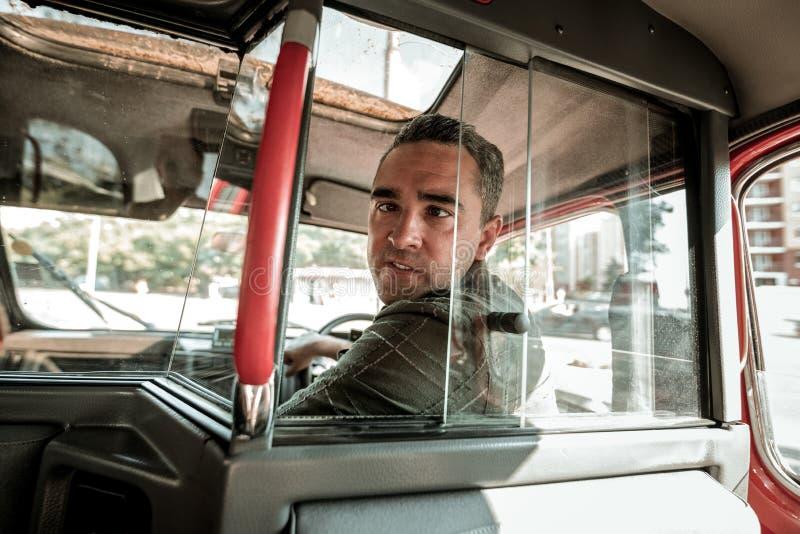 汽车司机做鬼脸的转动回到他的乘客 库存照片