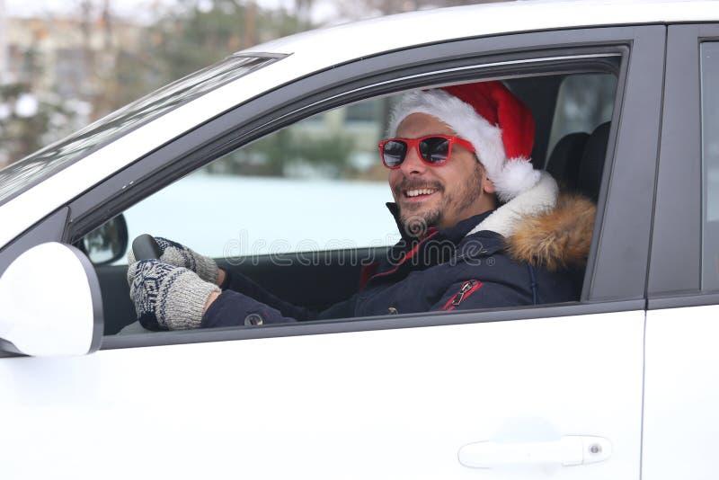 汽车司机画象与圣诞老人帽子和赞许享用的 免版税库存照片