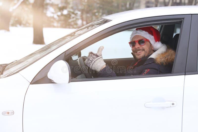 汽车司机画象与圣诞老人帽子和赞许享用的 库存图片