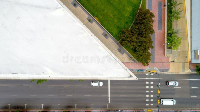 汽车在一张高楼鸟瞰图下通过一条被铺的路 免版税库存图片