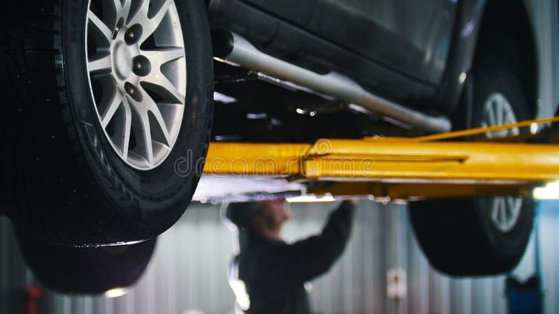 汽车在固定的,工作者修理细节汽车服务举了 免版税库存照片