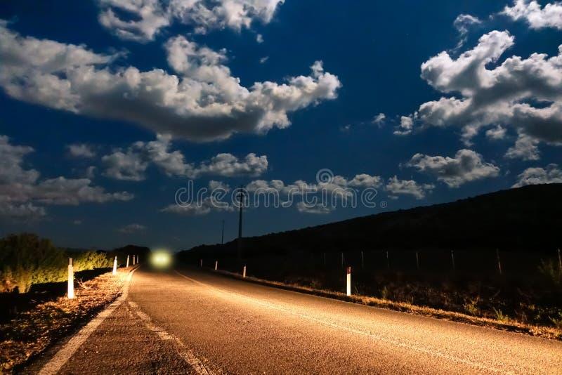 汽车在夜之前点燃来自黑暗-街道 免版税库存图片