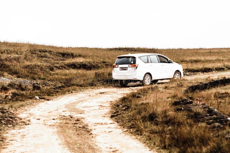 汽车在小山山的一个国家驾驶与在坏石渣路的急剧轮行动 由泥泞和溜滑的极端状态 图库摄影