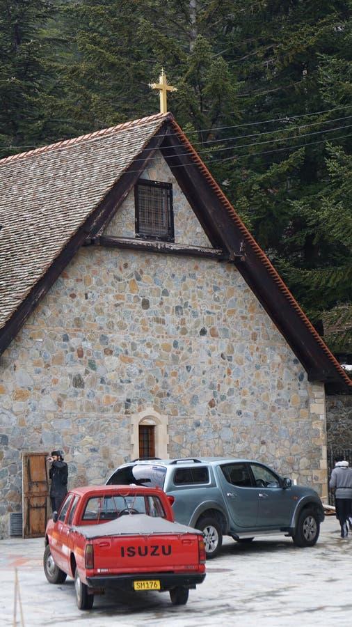 汽车在有一个十字架的一个石教会前面站立在塞浦路斯的屋顶在山 库存图片