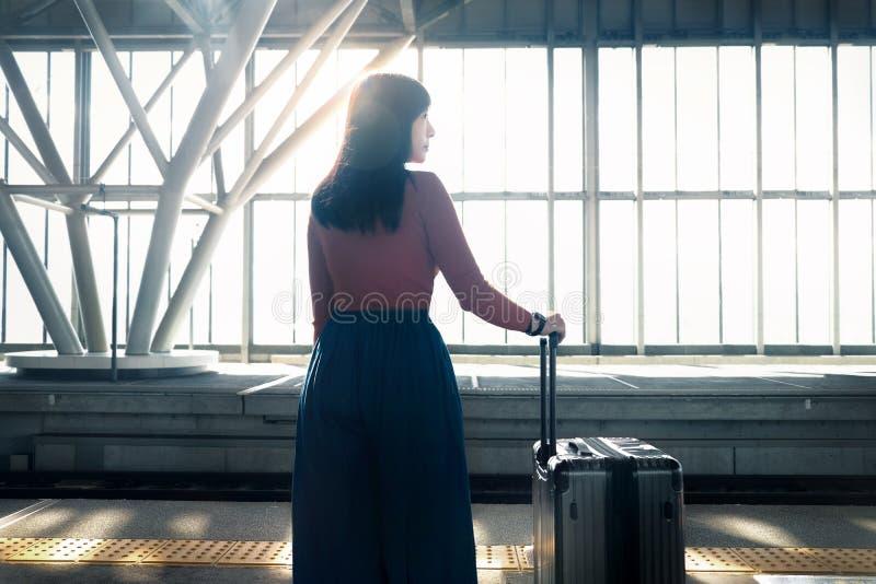 汽车城市概念都伯林映射小的旅行 等待带着在平台的手提箱的年轻女人在火车站 免版税库存照片
