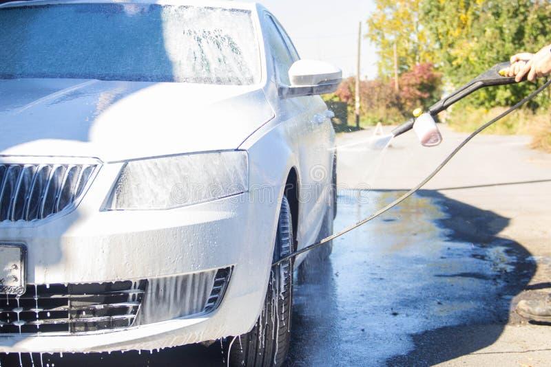 汽车干净的水管设备海绵洗涤 汽车干净的水管设备海绵洗涤 人洗涤汽车 免版税库存照片