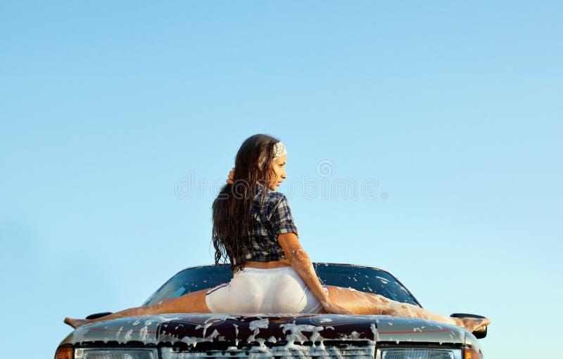 汽车性感泡沫的女孩坐日落年轻人 免版税库存照片