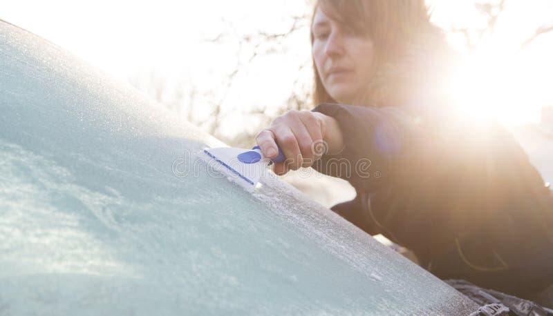 从汽车挡风玻璃的妇女刮的冰 免版税库存图片