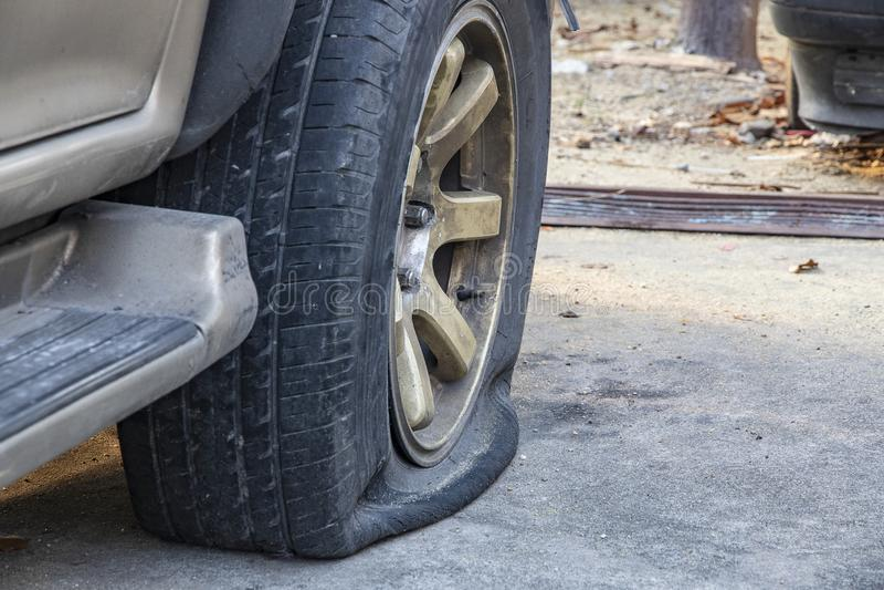 汽车损坏的泄了气的轮胎特写镜头在停车处的 库存照片