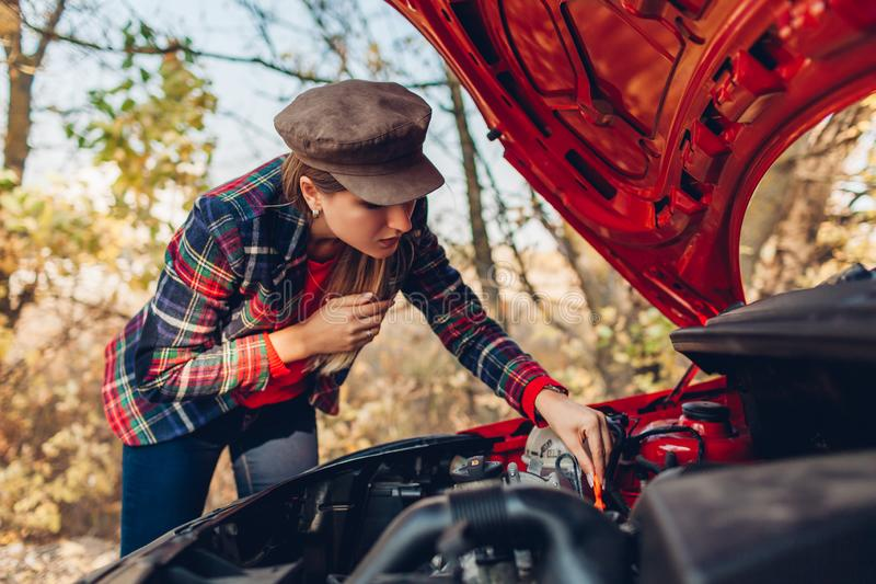 汽车损坏 女人打开汽车罩,在路上停下,检查机油水平 库存照片